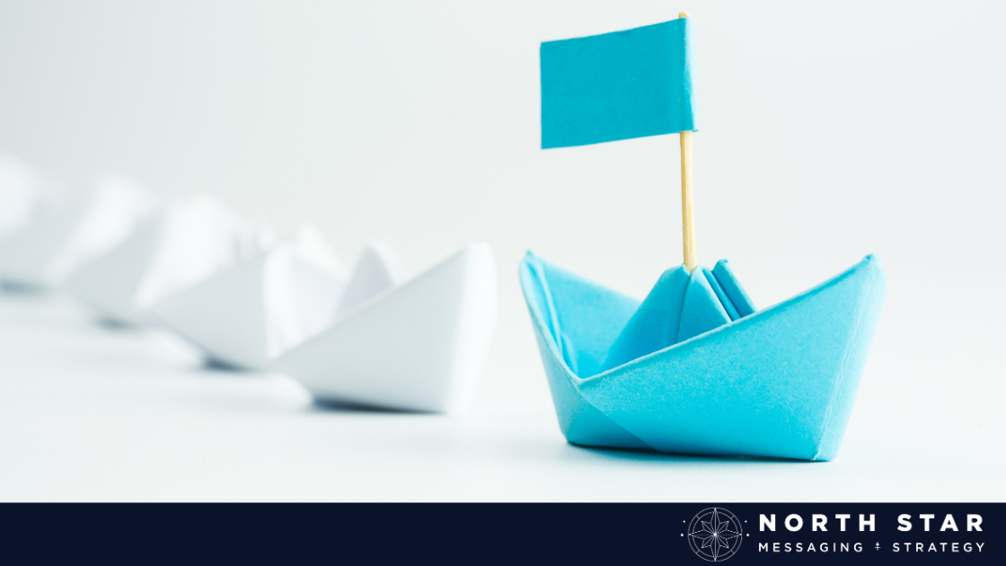 a blue paper boat leading a line of white paper boats